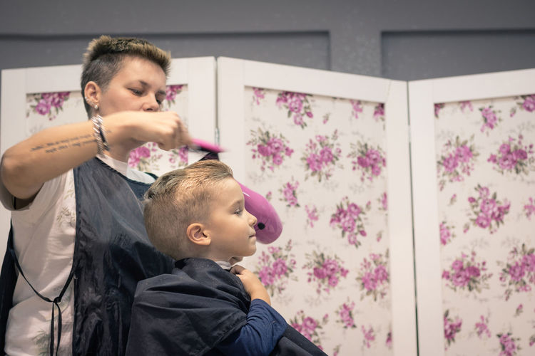 Barber blow drying hair of boy sitting on chair at shop