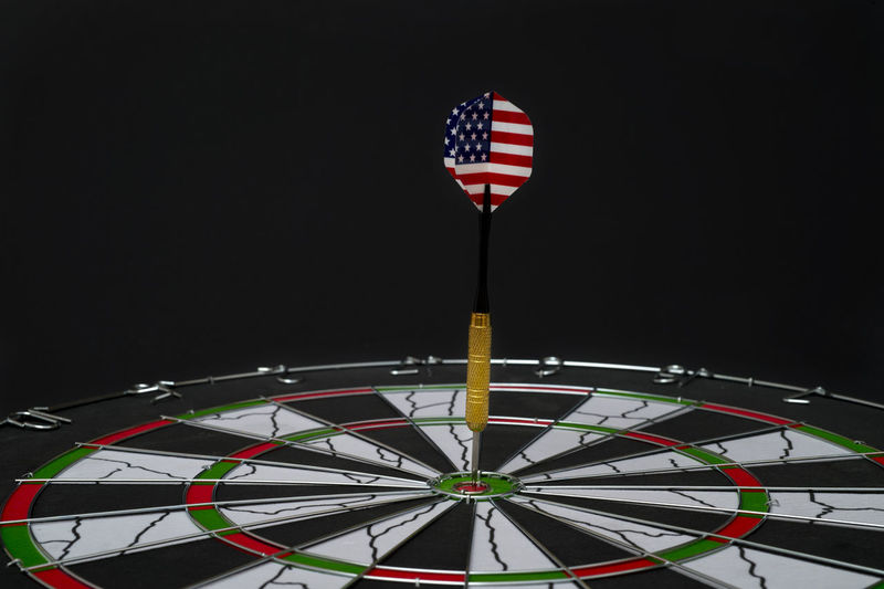 Center target of darts isolated on a black background Dartboard Bulls-eye Win Successful Center Public Metaphor Point Result Dart Targeting Victory Black Sport Board Mark Perfection Strategy Relations Conceptual Target Marketing Challenge Media Isolated American Circles Red Hit White Accuracy Objects Luck Accurate Perfect Arrow Patterns Ideas Game Flag Concept Direct Bull Success Eye Market Winner Background Play Patriotism No People Striped Night Black Background Studio Shot Shape Illuminated Arts Culture And Entertainment Copy Space Indoors  Leisure Activity Low Angle View Amusement Park