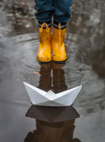 Boy standing in front of paper boat in puddle