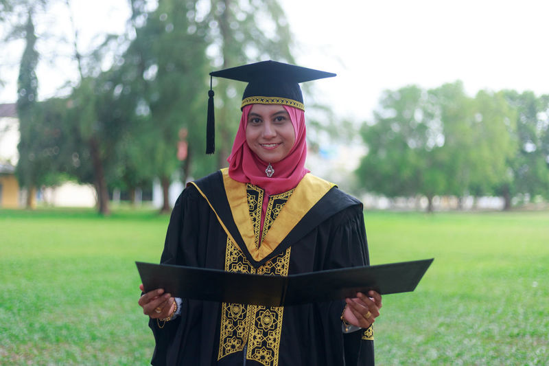 Portrait of smiling woman in graduation gown on field