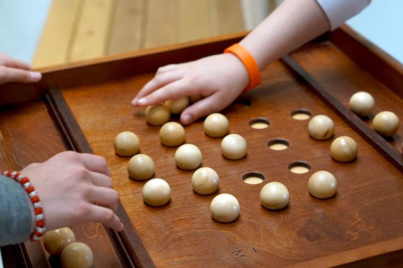 Cropped hands of people playing with wooden spheres