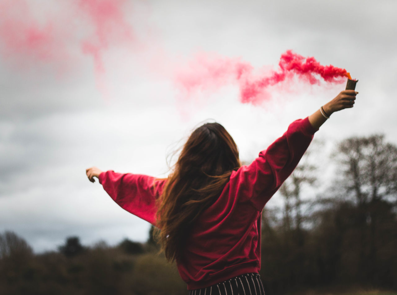 Rear View Of Happy Young Woman Holding Distress Flare While Standing On Field Against Sky