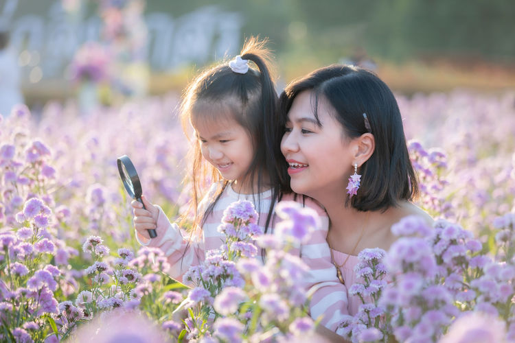 Close-up of daughter holding magnifying glass over purple flowering plants by mother