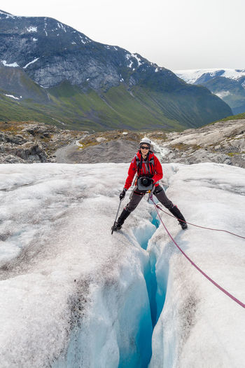 Happy female hiker standing on glacier crack against mountain