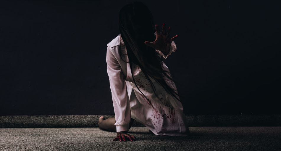Young woman with halloween make-up lying on floor in darkroom