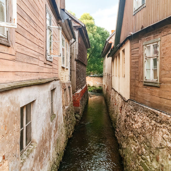 Aleksupite river winding through town, Kuldiga. Latvia Building Buildings Canal Deterioration Historic Kuldiga Latvia Narrow Old Old Buildings River Ruined Stream Summer Summertime Town Village Village Life Wooden