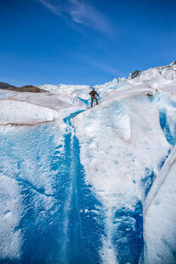 Low angle view of man standing at glacier against blue sky