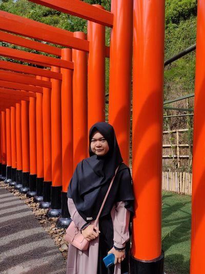 Portrait of teenage girl wearing hijab standing against orange columns