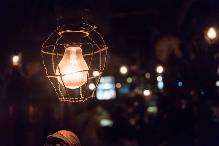 Close-up of illuminated light bulb at night