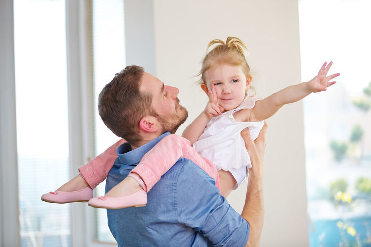 Cheerful father and daughter playing at home