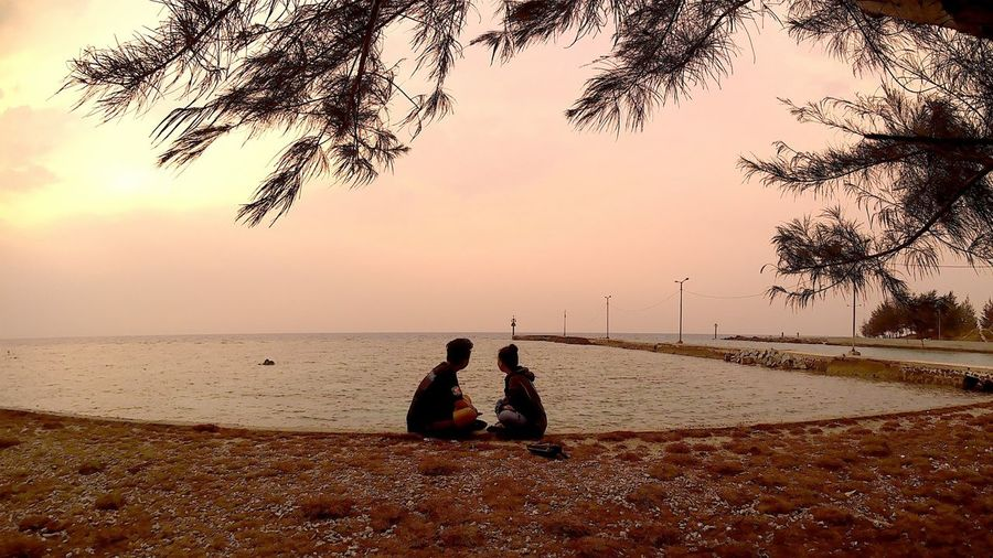 Side View Of Friends Looking At Sea Against Sky During Sunset
