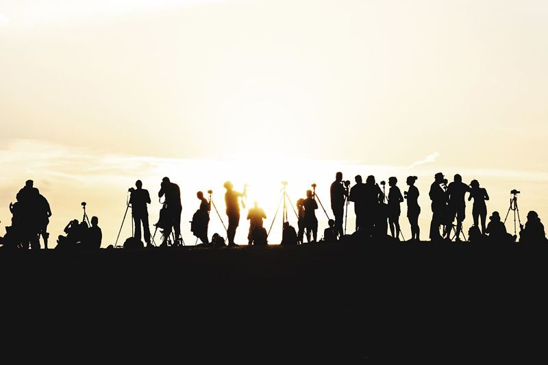 Silhouette people against clear sky during sunset
