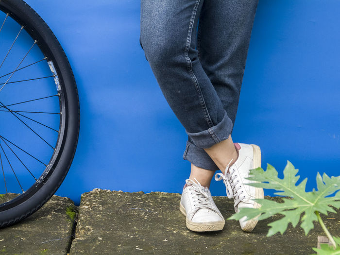 Low section of woman standing by bicycle against wall