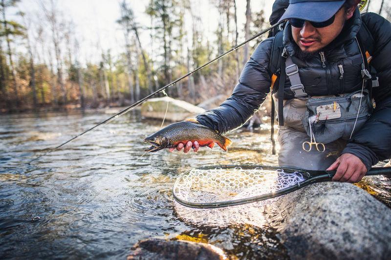 Man holding fish in lake