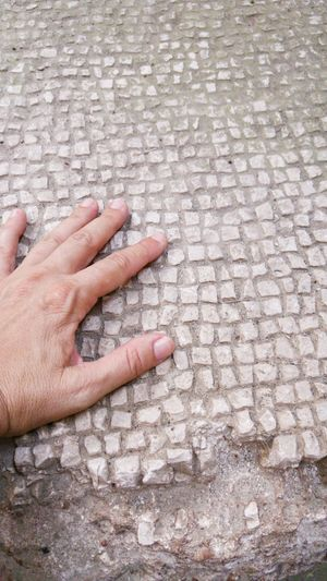 High angle view of hand on cobblestone street