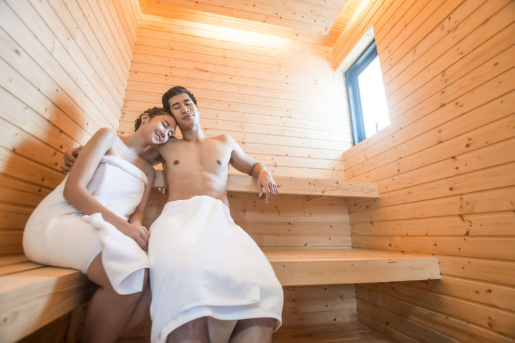 Couple Wrapped In Towels Sitting At Spa