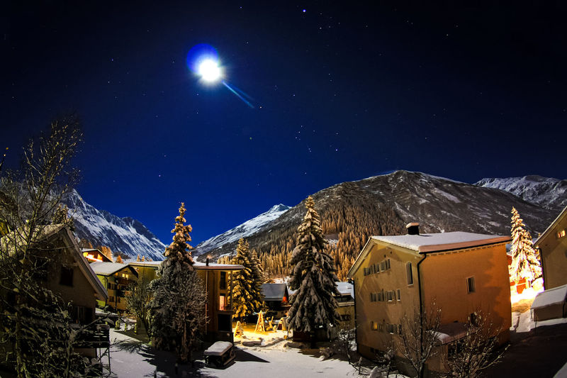 Snow covered buildings against sky at night
