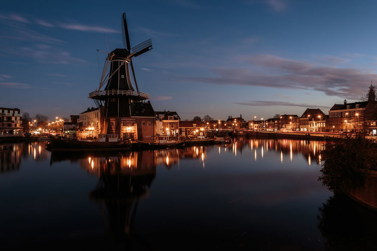 Traditional Windmill And Illuminated Buildings By Canal At Dusk