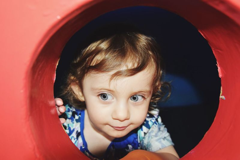 Little girl looks out of a playground porthole Colorful Peekaboo Peeking Cheeky Playing EyeEm Selects Childhood Child Portrait Looking At Camera Cute One Person Innocence Real People Indoors  Lifestyles Girls Baby Toddler  Front View Leisure Activity