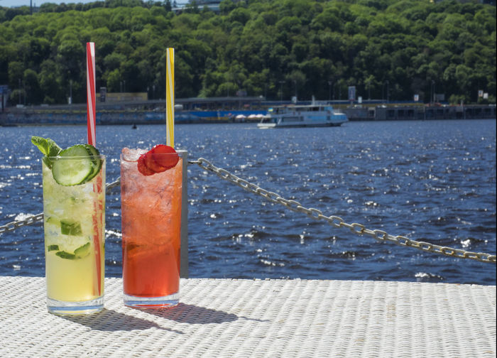 Close-up of lemonades in glasses on pier against sea