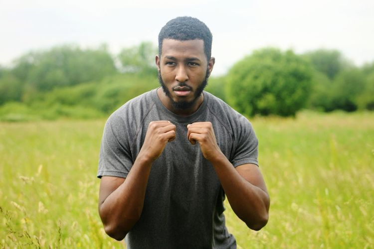 Young man in fighting stance standing on field