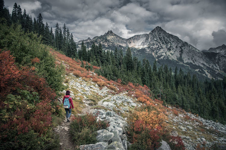Man with umbrella on mountain against sky