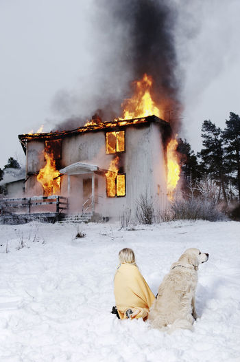 View of fire on snow covered field against building