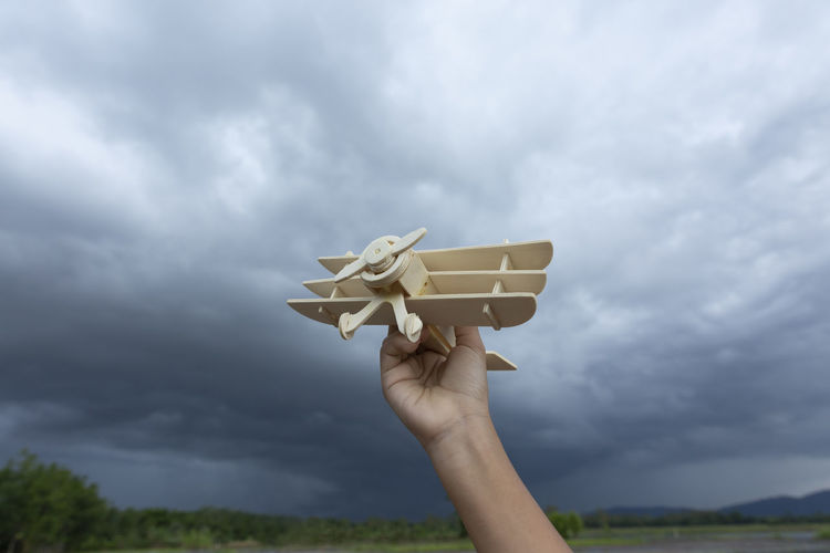 Cropped hand of person holding model airplane against cloudy sky