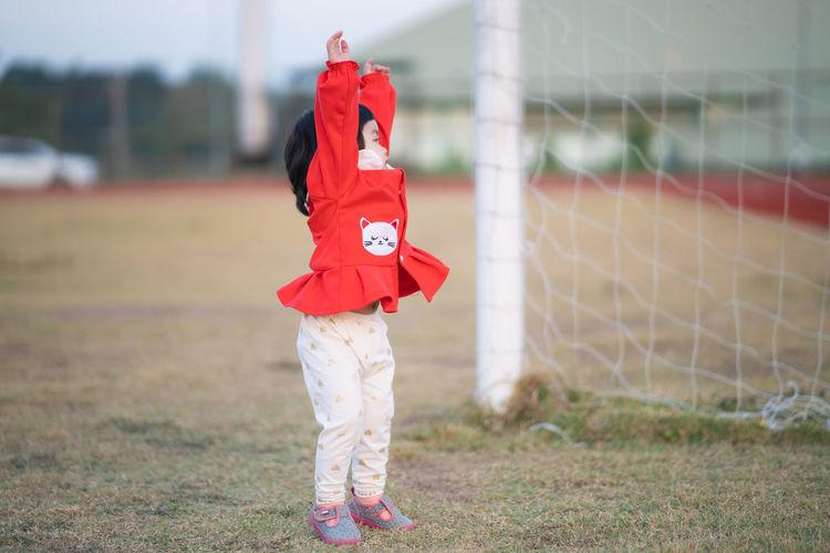 Full length of girl standing by soccer goal at field