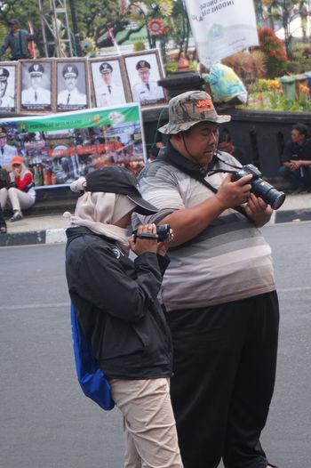 Full length of man using mobile phone on street