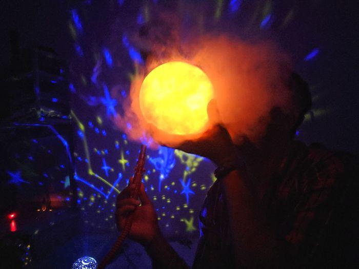 Full length portrait of man holding illuminated light at night