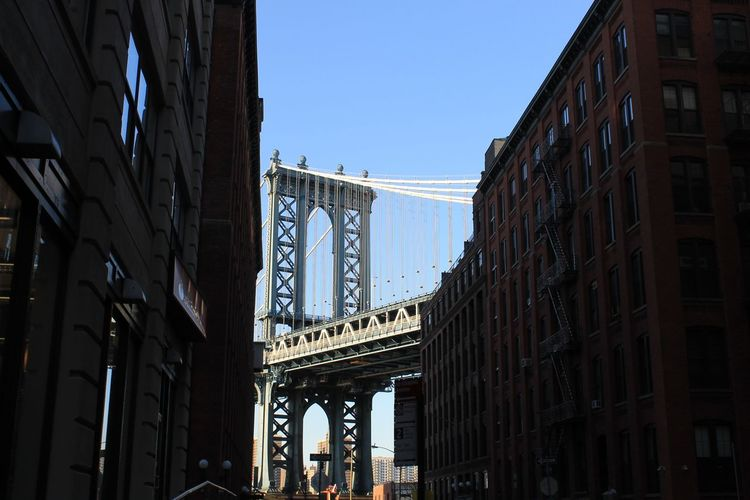 Low angle view of manhattan bridge and buildings against sky