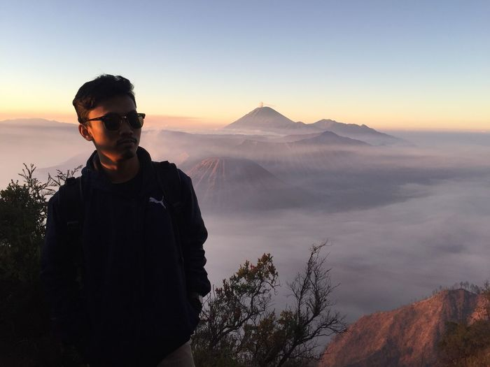 Young man standing by mountains against sky during sunset