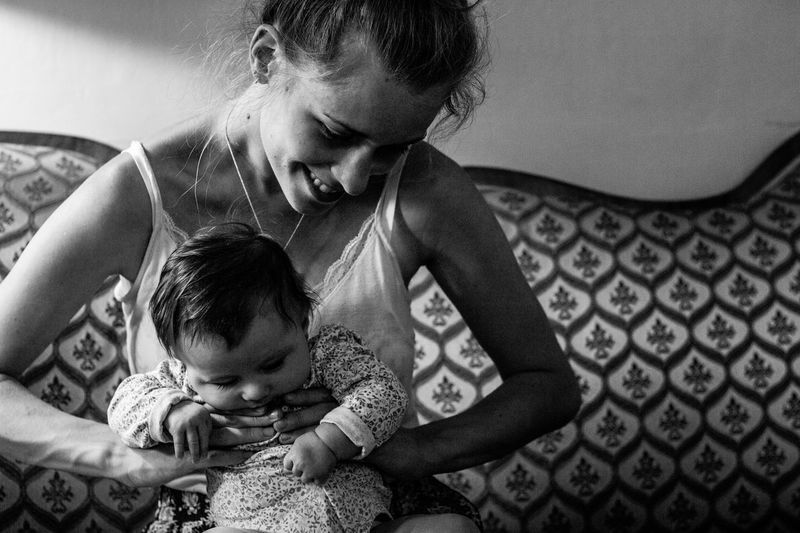 Smiling young woman holding daughter on sofa at home