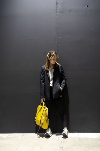 Businesswoman with backpack standing against wall at railroad station