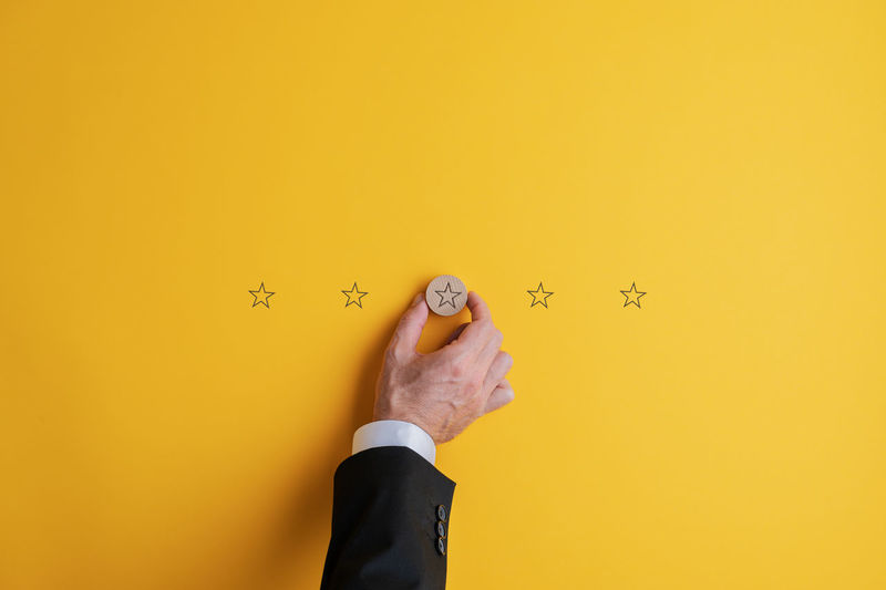 Portrait of man standing against yellow wall