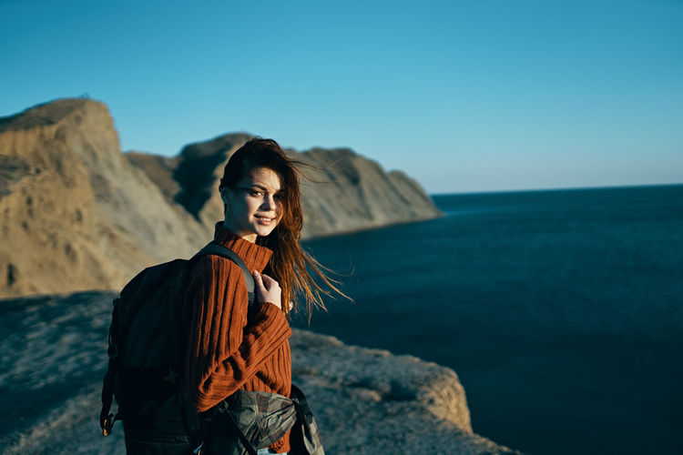 Young woman standing on rock by sea against sky