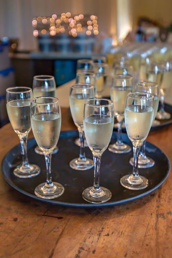 High Angle View Of Champagne Flutes Served On Wooden Table