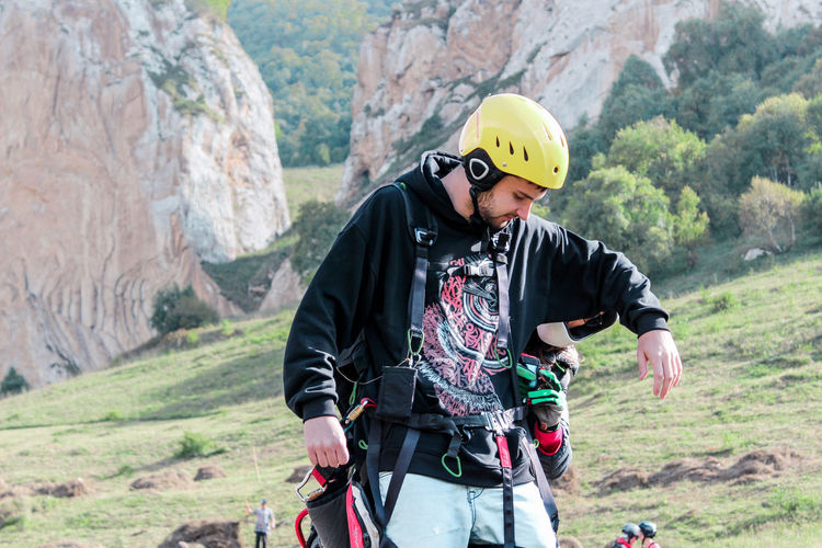 Expert helping man to put on safety harness