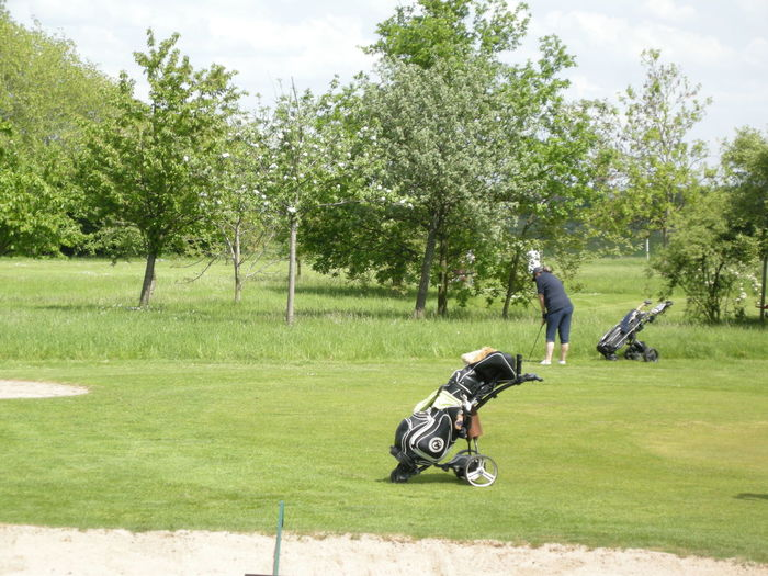 Woman playing while standing by golf bag at course