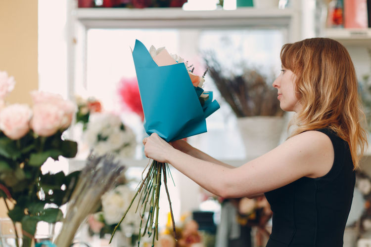Side view of woman holding flower bouquet while standing at home