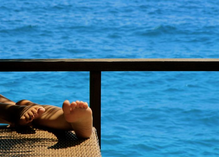 bare feet of woman against sea Barefoot Blue Close-up EyeEm Best Shots Female Foot Human Body Part Legs Lifestyles Light And Shadow Maldives Toes Ocean Outdoors People Railing Relaxing Sea Skin Summer Table Vacation Water Woman Miles Away Done That. Modern Hospitality