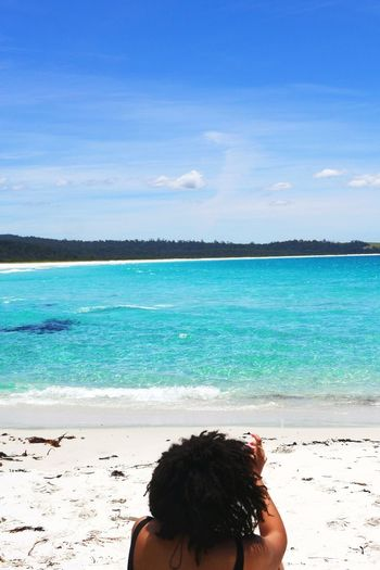 Rear view of boy on beach against blue sky