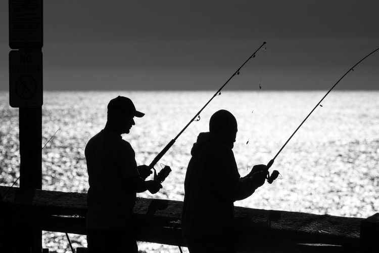 Silhouette people fishing at sea against clear sky