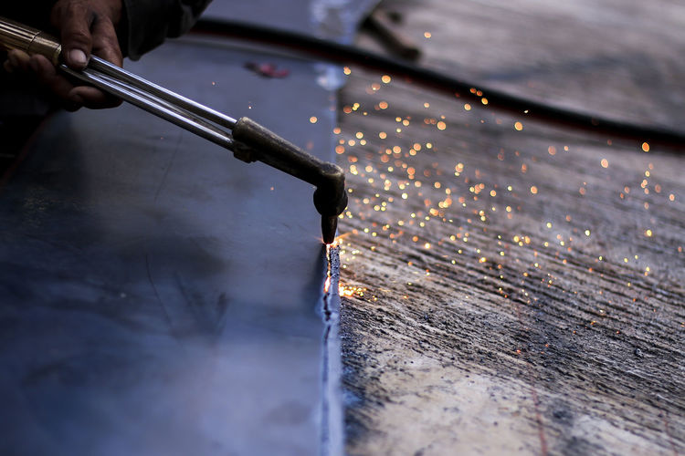 Cropped hand welding metal in workshop