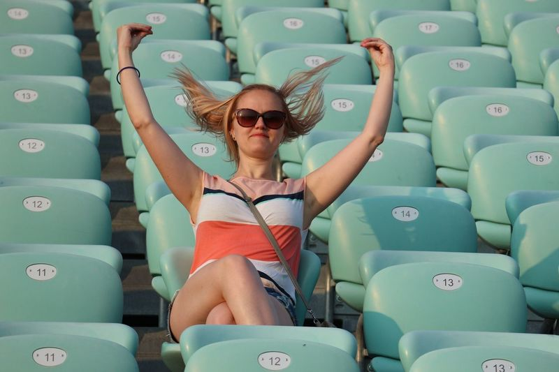 Low angle view of woman tossing hair while sitting on seat at stadium