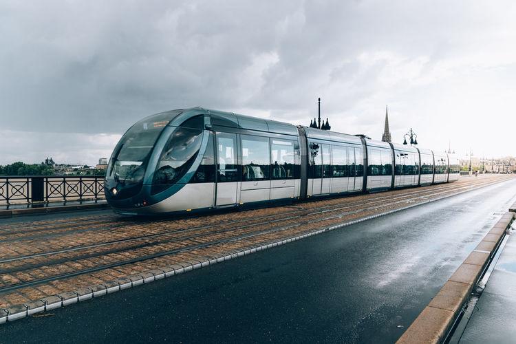 Train on bridge in city against sky