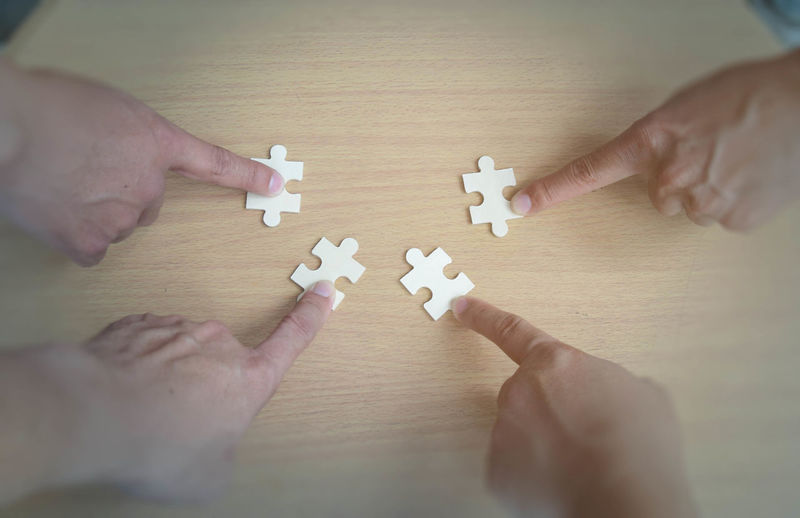 Group of business people assembling jigsaw puzzle wanting to put pieces of puzzle together on wood table backgroung for help support, teamwork concept Together Business SUPPORT Strategy Game Teamwork Unity Assembling Building Communication Connection Cooperation Cooperation Wins The Race Drive Finger Hand Holding Jigsaw  Jigsaw Piece Jigsaw Puzzle Partnership Puzzle  Puzzle  Strategy Success Teamwork