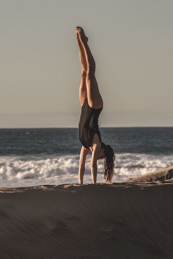 Full length of woman doing handstand at beach