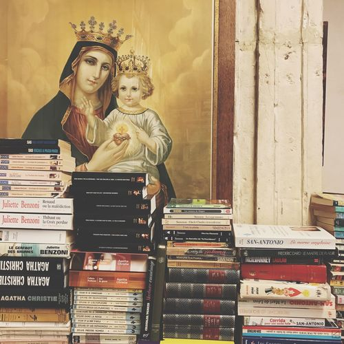 Icon and books Wall Hanging Wall Decor Religious  Icon Bookstore Books EyeEm Selects Two People Stack Retail  Indoors  Day